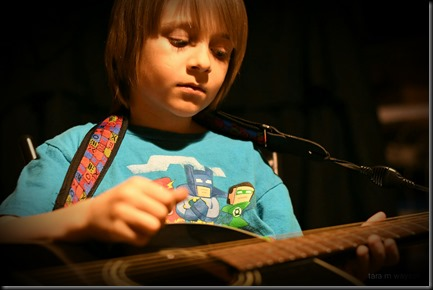 warm light on face of boy strumming guitar